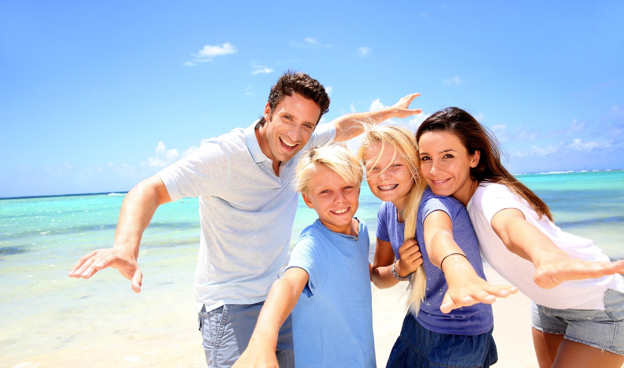 Familie met kinderen op het strand